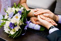 Groom gently holding the hand of the bride note wedding bouque bouquet out focus Stock Photography