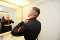 Groom getting ready a young military man for his wedding looking in mirror Royalty Free Stock Image