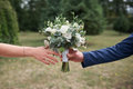 Groom gives the bride a beautiful bridal bouquet on the walk Royalty Free Stock Photo