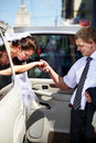 Groom helping his bride out of wedding limo Stock Photo