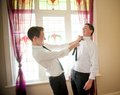 Groom and his best man joking and playing while they dress up get ready for the wedding Stock Images