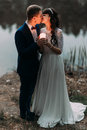 Groom and his charming new wife kissing on the shore of forest lake at evening Royalty Free Stock Photo