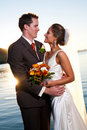 Groom holding bride at sunset with sunburst Royalty Free Stock Image