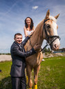 Groom holding horse with bride in saddle by rein Stock Photography