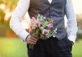 Groom holding wedding bouquet part of the in hand Royalty Free Stock Photography