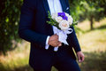 Groom holding a wedding bouquet Royalty Free Stock Photo