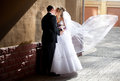 Groom hugging bride while wind lifting veil full length portrait of Stock Photo
