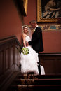 Groom hugging young bride on stairs in old castle handsome Royalty Free Stock Image