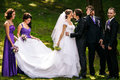 Groom kisses a bride while his friends grimaces behind him Stock Image