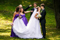 Groom kisses a bride while his friends grimaces behind him Stock Photos