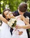 Groom kissing bride on shoulder outdoor Stock Images
