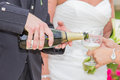 Groom pooring champagne on a glass grooms hand at wedding reception Royalty Free Stock Photo