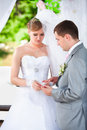 Groom putting wedding ring on brides hand at alcove Royalty Free Stock Photo