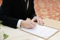 Groom signing marriage license or wedding contract close up Royalty Free Stock Photos