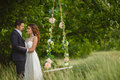 Groom swings the bride on a swing in outdoor park newlyweds their wedding day fun summer green rolls decorated with flowers Stock Images