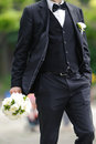 Groom walking in park with wedding bouquet Royalty Free Stock Photo
