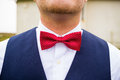 Groom wearing bowtie a fashionable wears a red and white with a navy blue vest on his wedding day Royalty Free Stock Photography