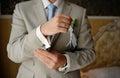 Groom wears cufflinks in hotel Royalty Free Stock Images