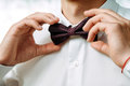 The groom in a white collar fixing his bow tie Royalty Free Stock Photo