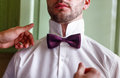 The groom in a white shirt fixing his bow tie Royalty Free Stock Photo