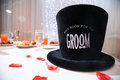 Grooms top hat on table at wedding reception with petals scattered in foreground Stock Photography