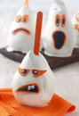 Grotesque halloween ghost edible decoration with a sneering toothy expression made from a pear coated in white chocolate or Stock Images