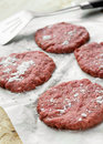 Ground beef burgers four raw on the wax paper Stock Image