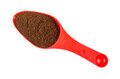 Ground coffee in red plastic spoon isolated on white Royalty Free Stock Photo