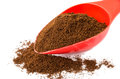 Ground coffee in red spoon and heap of coffee Royalty Free Stock Photo