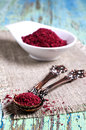 Ground sumac in a metal spoon on a wooden surface Stock Photo