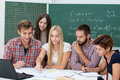 Group activity in the classroom with a diverse multiethnic of college or university students gathered together at a table Royalty Free Stock Photo