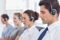 Group of agents sitting in line in a call centre bright Royalty Free Stock Photo