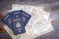 Group of american passports with foreign banknotes four in different currencies lying on a wooden table depicting planning and Royalty Free Stock Images
