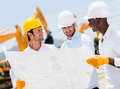 Group of architects at a construction site looking blueprints Royalty Free Stock Photos