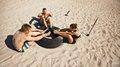 Group of athletes doing crossfit exercise routine on beach fitness and healthy lifestyle small young abdominal with a truck tire Stock Photography