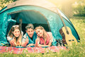 Group of best friends with thumbs up in camping tent having fun together concept carefree youth and freedom outdoors the nature Royalty Free Stock Photography