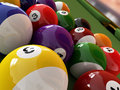 Group of billiard balls with numbers on green pool table a hole in the background close up view Stock Image