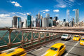 Group of blurred typical yellow New York cabs crossing the Brooklyn Bridge with the Manhattan skyline with blue sky with few cloud Royalty Free Stock Photo