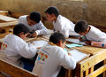 Group of boys in class writing homework sitting on desk arabic wooden doing activities together and helping each other photo Royalty Free Stock Images