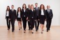 Group of business executives approaching large diverse walking towards the camera led by a smiling woman Royalty Free Stock Image