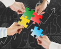 Group of business people assembling colorful jigsaw puzzles Royalty Free Stock Photo