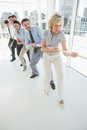 Group of business people pulling rope in office full length a a bright Stock Photo