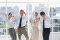 Group of business people raising arms as a success in their workplace Stock Photography