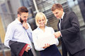 Group of business people standing outside modern building with c Royalty Free Stock Photo