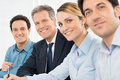 Group of businesspeople portrait happy looking at camera sitting in a row at office Stock Photography