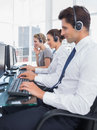 Group of call center employees working in line a bright office Royalty Free Stock Image