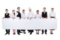 Group of catering staff holding a blank banner large with copyspace for your text including chef waiters waitresses hostess and Royalty Free Stock Images