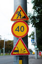 Group cautionary road signs of on column near the warning about repairing about speed limits and about danger of stones shooting Royalty Free Stock Images