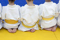 Group of children in kimono sitting on tatami on martial arts training seminar selective focus Royalty Free Stock Images
