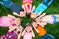 A group of children lying on the green grass in the Park. The interaction of the children. Royalty Free Stock Photo